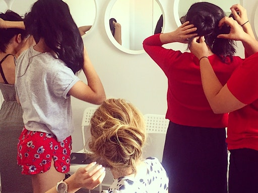 Participants practicing hairstyling